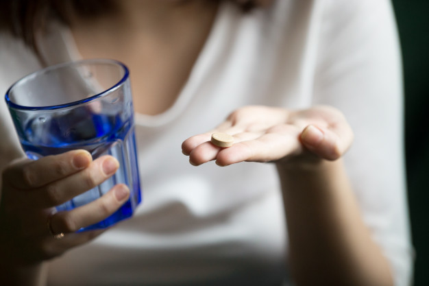 female-hands-holding-pill-glass-water-closeup-view_1163-4878